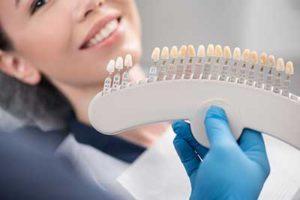 A dentist shows his patient dental veneers in TX