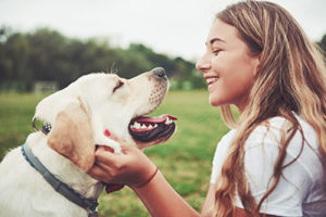A girl plays with her dog and smiles after she has a teeth cleaning in Sharpstown, TX