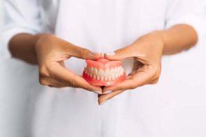 dentist holding a full pair of dentures