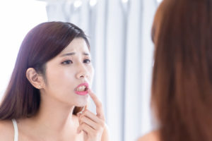 a woman checks her teeth in the mirror and wonders how does tooth decay develop