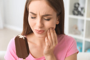 a woman holding an ice cream bar thinks about common dental problems