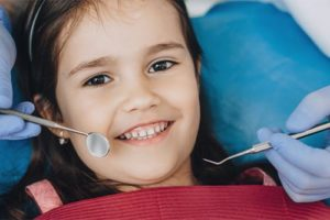 a little girl is happy to be receiving pediatric dentistry care